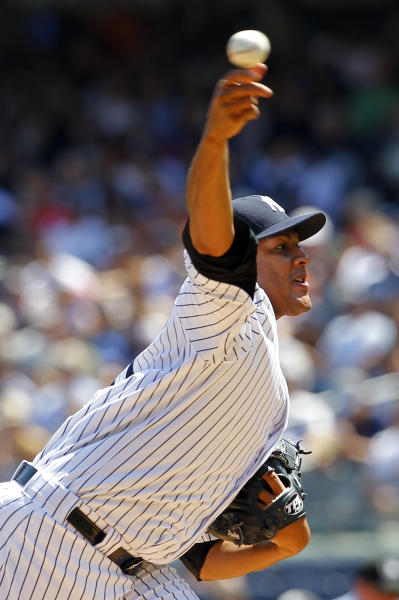 New York Yankees pitcher Ivan Nova throws a pitch against the Texas Rangers in the first inning of their Major League Baseball game at Yankee Stadium in New York, Thursday, August 16, 2012. (AP Photo/Paul J. Bereswill)