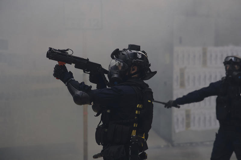 Police use tear gas on protesters calling for electoral reforms and a boycott of the Chinese Communist Party in Hong Kong, Sunday, Jan. 19, 2020. Hong Kong has been wracked by often violent anti-government protests since June, although they have diminished considerably in scale following a landslide win by opposition candidates in races for district councilors late last year. (AP Photo/Ng Han Guan)