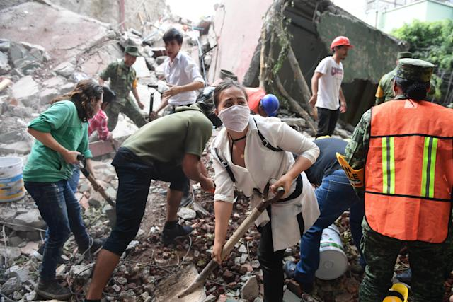 Volunteers use shovels to remove debris and search for survivors.