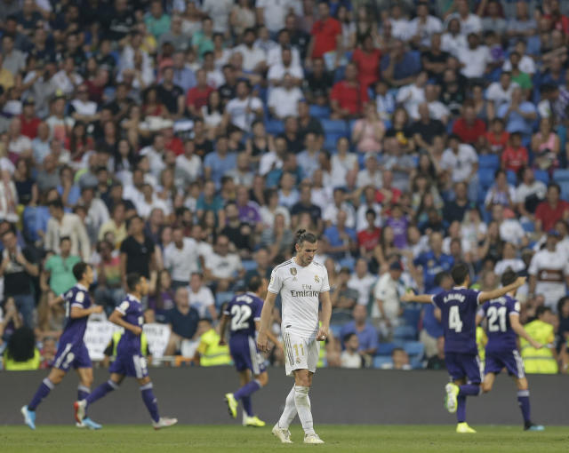 Real Madrid's Gareth Bale reacts as Valladolid's Sergi Guardiola celebrates after scoring his side's first goal during the Spanish La Liga soccer match between Real Madrid and Valladolid at the Santiago Bernabeu stadium in Madrid, Spain, Saturday, Aug. 24, 2019. (AP Photo/Paul White)