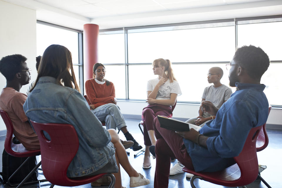 Depressed young woman sharing while sitting with friends and mental health instructor in group meeting at classroom