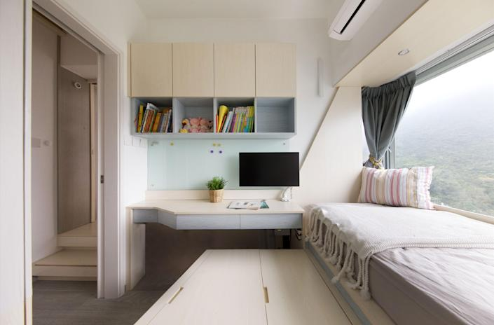 In the child's bedroom, the wooden platform doubles as a seat for the built-in desk for a convenienthomework station.