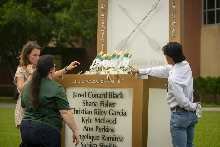 """Corrigan Garcia, who graduated from Santa Fe High School in 2018, and Maegan Huddleston, who graduated in 2019, and Megan Grove, who chair's the Santa Fe Ten Memorial Foundation, place ten feathers representing the ten victims of the 2018 Santa Fe school shooting on the new memorial to the ten victims, Tuesday, May 18, 2021, outside of the high school in Santa Fe, Texas. The Santa Fe Ten Memorial Foundation unveiled the """"Unfillable Chair,"""" a student designed memorial, on the third anniversary of the shooting. The foundation is planning a larger memorial for the future. (Mark Mulligan/Houston Chronicle via AP)"""
