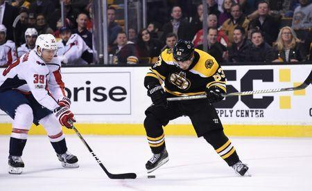 Dec 14, 2017; Boston, MA, USA; Boston Bruins left wing Brad Marchand (63) and Washington Capitals right wing Alex Chiasson (39) battle for the puck during the third period at TD Garden. Mandatory Credit: Bob DeChiara-USA TODAY Sports
