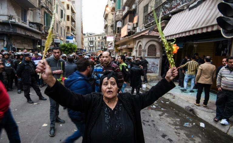 An Egyptian woman raises braided palm leaves, originally intended for Palm Sunday celebrations, during a gathering outside the Coptic Orthodox Patriarchate in Alexandria after a bomb blast struck outside while worshippers attended Palm Sunday mass on April 9, 2017