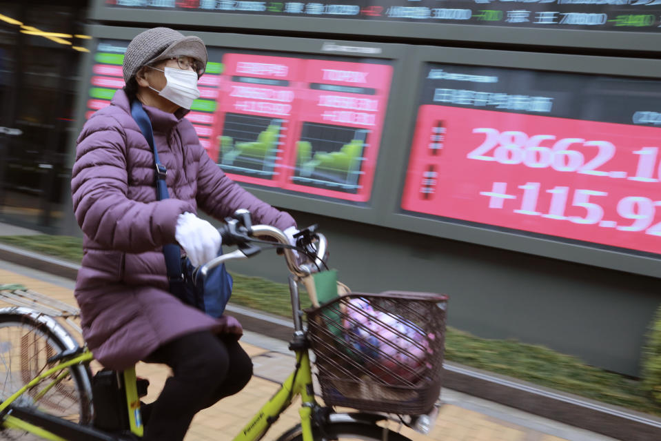 A woman cycles past by an electronic stock board of a securities firm in Tokyo, Wednesday, Jan. 27, 2021. Stocks were mixed in Asia on Wednesday after a lackluster session on Wall Street. (AP Photo/Koji Sasahara)