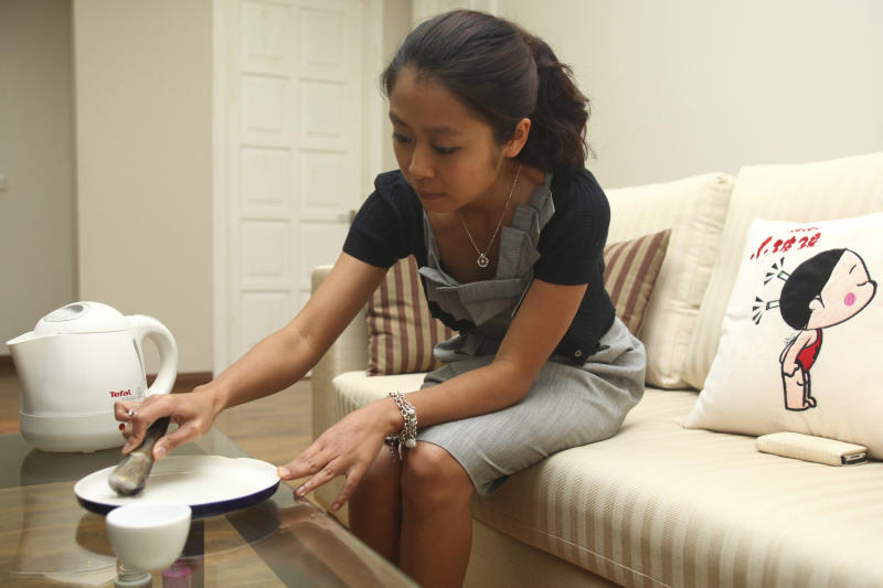 In this photo taken on 13 March 2012, Nguyen Huong Giang, 24, grinds rhinoceros horn with water at her apartment in Hanoi, Vietnam, demonstrating how she makes a liquid concoction she ingests after drinking too much alcohol or when suffering from allergies. Wildlife conservationists warn that Vietnam's surging demand for such horns, which are believed to treat everything from hangovers to cancer, is threatening to wipe out the world's remaining rhino populations. Illegal killings in Africa hit a record high in 2011 and are expected to worsen this year. (AP Photo/Na Son Nguyen)