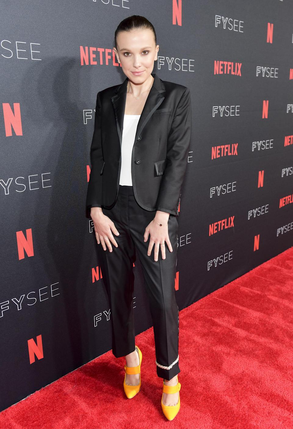<p>The Calvin Klein muse looked chic in a black suit and white top which she wore with patent yellow heels to add a pop of colour. <em>[Photo: Getty]</em> </p>