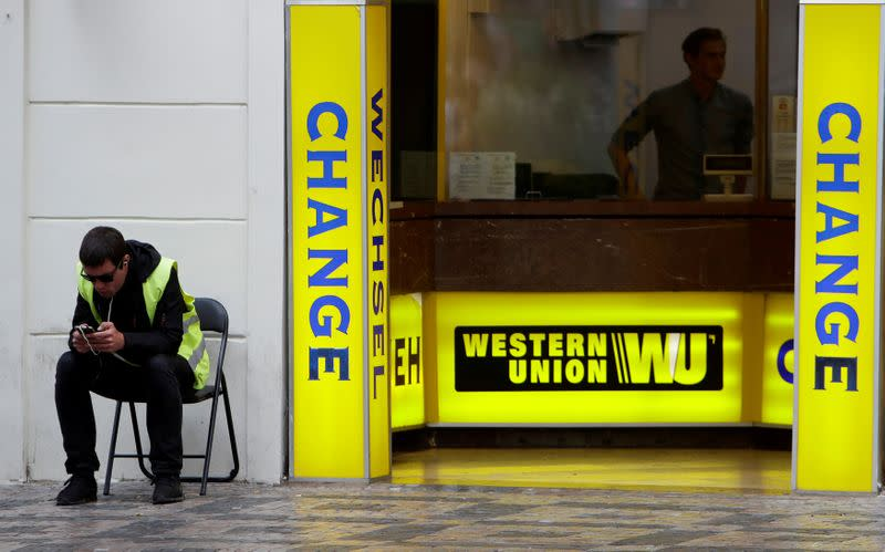 FILE PHOTO: A man sits on a chair next to Western Union currency exchange office in Prague