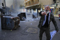 A protester shouts slogans in front of burning garbage containers used to block a main road during a protest against the increase in prices of consumer goods and the crash of the local currency, in Beirut, Lebanon, Tuesday, March 16, 2021. Scattered protests broke out on Tuesday in different parts of the country after the Lebanese pound hit a new record low against the dollar on the black market. (AP Photo/Hussein Malla)