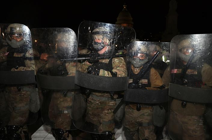 """Members of the National Guard assist police officers in dispersing the mob of Trump supporters who were gathering at the Capitol.<span class=""""copyright"""">Tasos Katopodis—Getty Images</span>"""