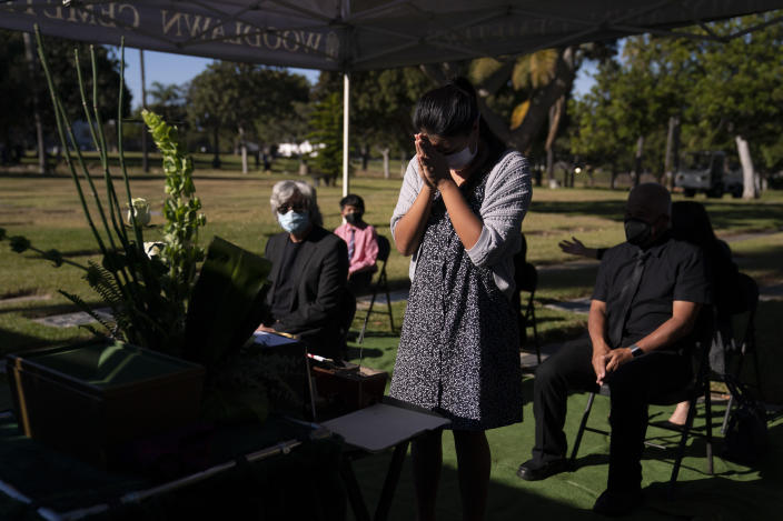 Lilah Matsumura, 11, prays for for her great-grandfather, Giichi Matsumura, during a memorial service at Woodlawn Cemetery in Santa Monica, Calif., Monday, Dec. 21, 2020. Giichi Matsumura, who died in the Sierra Nevada on a fishing trip while he was at the Japanese internment camp at Manzanar, was reburied in the same plot with his wife 75 years later after his remains were unearthed from a mountainside grave. (AP Photo/Jae C. Hong)