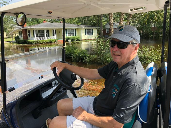 Joe Holmes rides his golf cart around neighborhoods to survey floodwaters in Conway, S.C., on Monday, Sept. 17, 2018. Holmes barely avoided the flooding in 1999 and 2016, but worries a decision by the state of South Carolina to build a higher wall on the main highway to Myrtle Beach to keep it open might finally push the floodwaters from the Waccamaw River into his house. The state says the effect will be negligible. (AP Photo/Jeffrey Collins)
