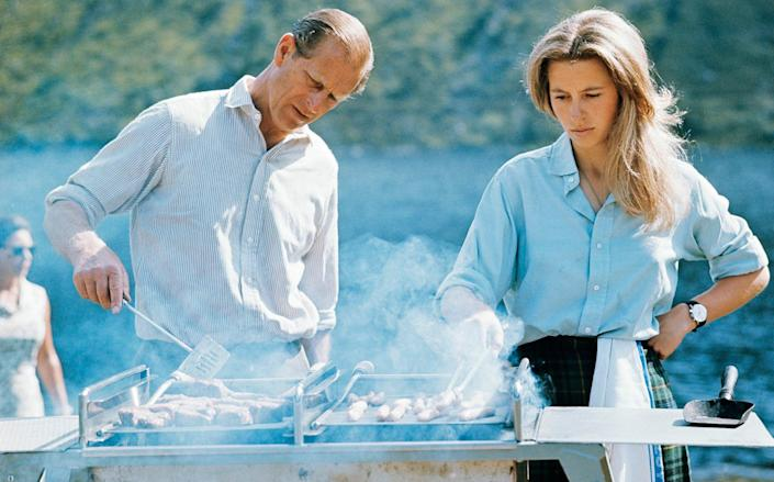 HRH The Duke of Edinburgh and HRH The Princess Anne preparing a barbecue on the Estate at Balmoral Castle, Scotland during the Royal Family's annual summer holiday, 22nd August 1972. - Lichfield/Getty Images