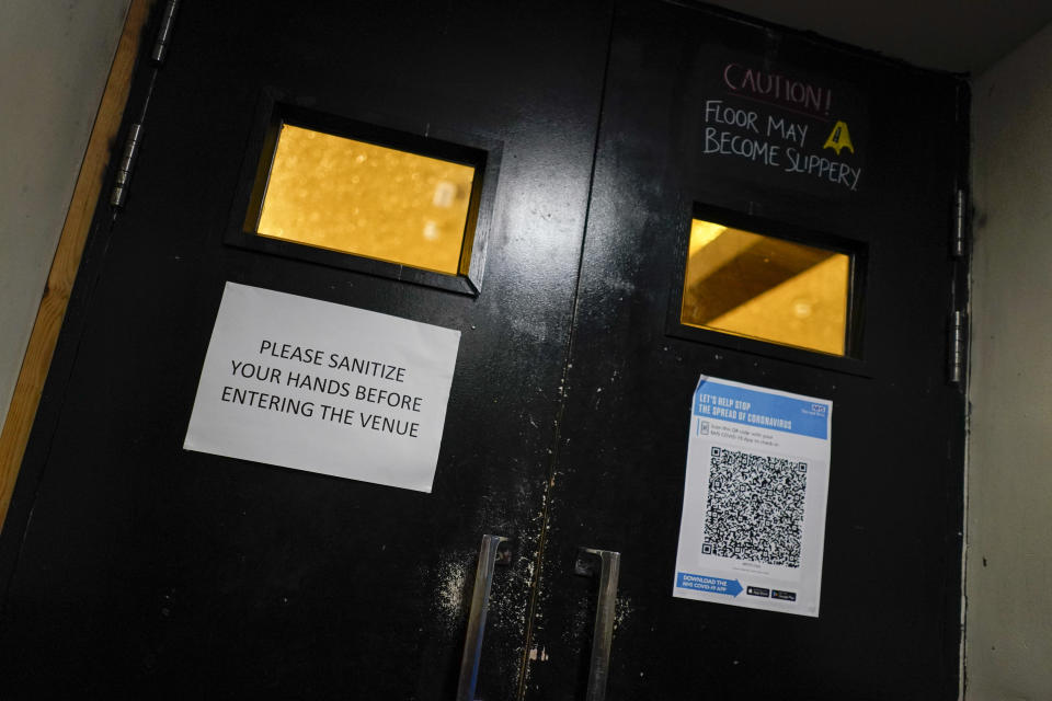 A sign attached on the entry door to the Moth Club in Hackney asks patrons to sanitize hands upon entry in London, Sunday, May 30, 2021. The return of live music in the city that produced bands from the Rolling Stones to the Spice Girls has reignited the creativity of some of London's many working artists after 14 months of silence. Jack Milwaukee says his inspiration to create new music was reduced to zero during the pandemic, but it returned once the road map for reopening was clear. Musicians started playing again across London on May 17, but to small, socially distanced crowds. (AP Photo/Alberto Pezzali)