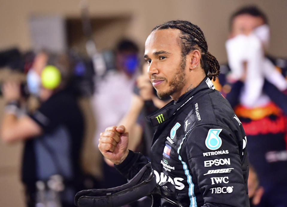 FILE - In this Sunday, Nov. 29, 2020 file photo Mercedes driver Lewis Hamilton of Britain celebrates after wining the Formula One race in Bahrain International Circuit in Sakhir, Bahrain. World champion Lewis Hamilton tested positive for COVID-19 and will miss the Sakhir Grand Prix this weekend, his Mercedes-AMG Petronas F1 Team said Tuesday Dec. 1, 2020. (Giuseppe Cacace, Pool via AP, File)