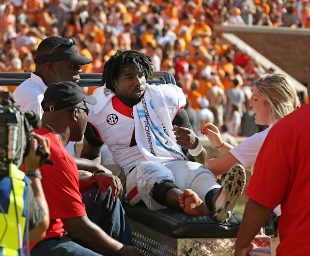 Georgia's Keith Marshall (4) is carted off of the field after getting injured during the first half of an NCAA college football game in Knoxville, Tenn., Oct. 5, 2013. (AP Photo/Atlanta Journal-Constitution, Jason Getz)