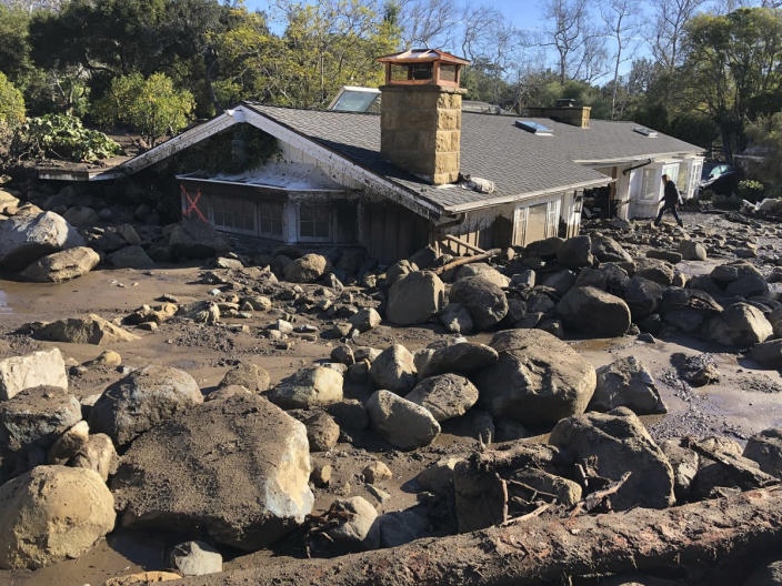 <p>Kerry Mann navigates the large boulders and mudflow that destroyed the home of her friend in Montecito, Calif., Wednesday, Jan. 10, 2018. The woman who lives in the home has not been seen since the early hours of Tuesday. (Photo: Mike Eliason/Santa Barbara County Fire Department via AP) </p>