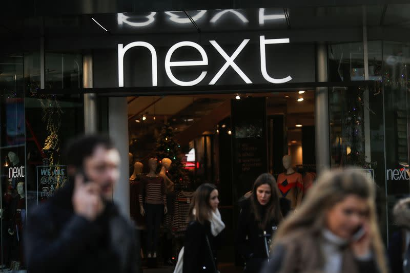 FILE PHOTO: Shoppers walk past a Next store on Oxford Street in London