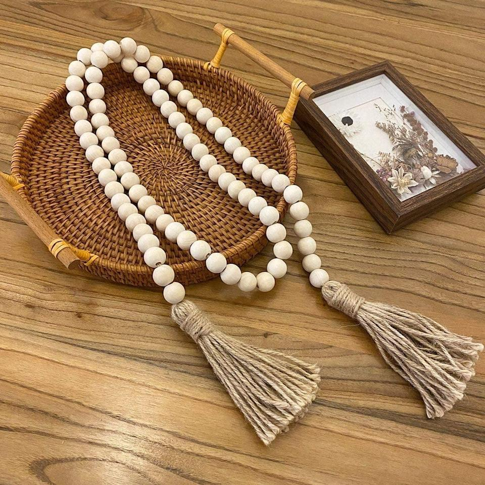<p>Add a dash of rustic vibes with these <span>Farmhouse Beads Wood Bead Garland with Tassels </span> ($11). Use them to add accents to a entrance table or frame a wall. You can even use them to tie your curtains back so you can enjoy the natural sunlight during work hours. </p>