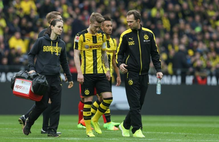 Dortmund's forward Marco Reus (C) goes off injured during the German First division Bundesliga football match between Borussia Dortmund and Bayer 04 Leverkusen in Dortmund, western Germany, on March 4, 2017