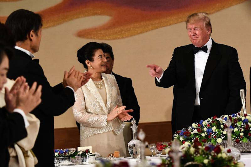President Donald Trump gestures standing next to Japan's Empress Masako during a state banquet at the Imperial Palace in Tokyo on May 27, 2019.