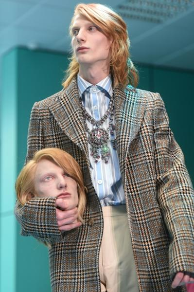A Gucci model holds a replica of his own head on the runway