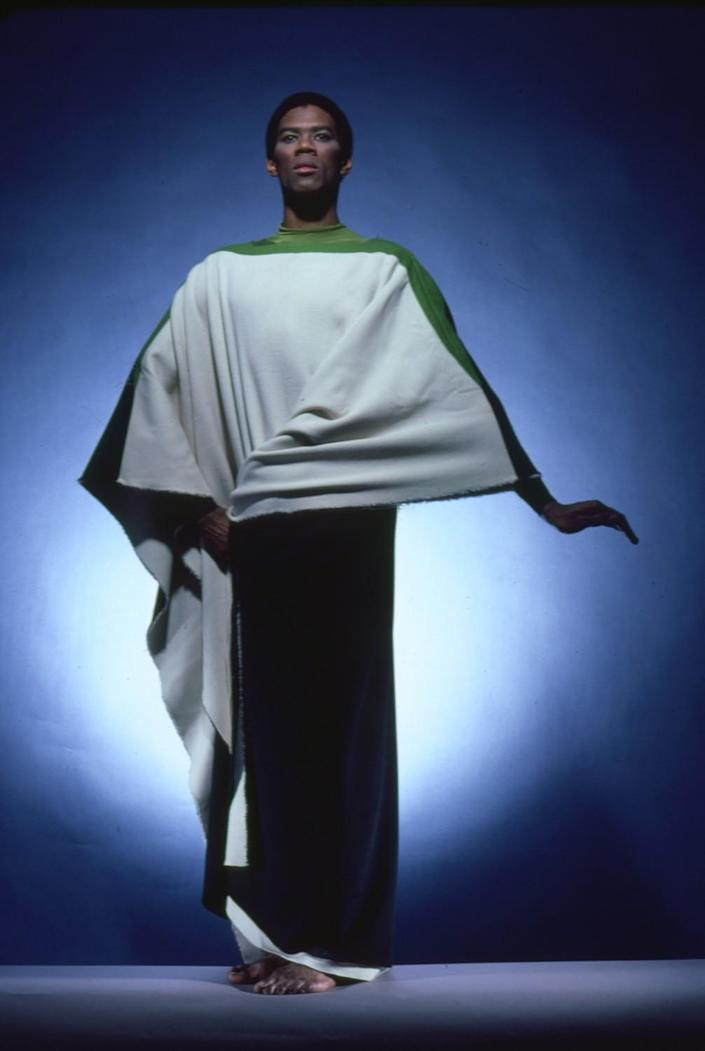 A dancer wearing a draped white and green costume.