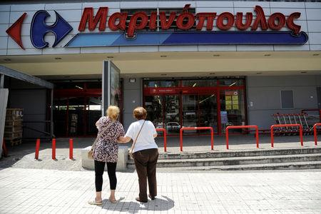 Two women stand in front of a Marinopoulos supermarket, while the Greek retail group Marinopoulos applies for creditor protection, in Athens