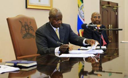 Uganda's President Yoweri Museveni signs an anti-homosexual bill into law at the state house in Entebbe