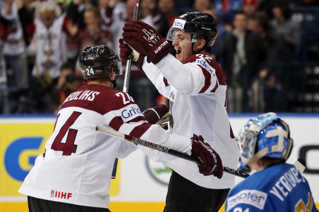 Latvia defender Arturs Kulda, right, and forward Mikelis Redlihs celebrate a goal during the Group B preliminary round match between Latvia and Kazakhstan at the Ice Hockey World Championship in Minsk, Belarus, Tuesday, May 13, 2014. (AP Photo/Darko Bandic)