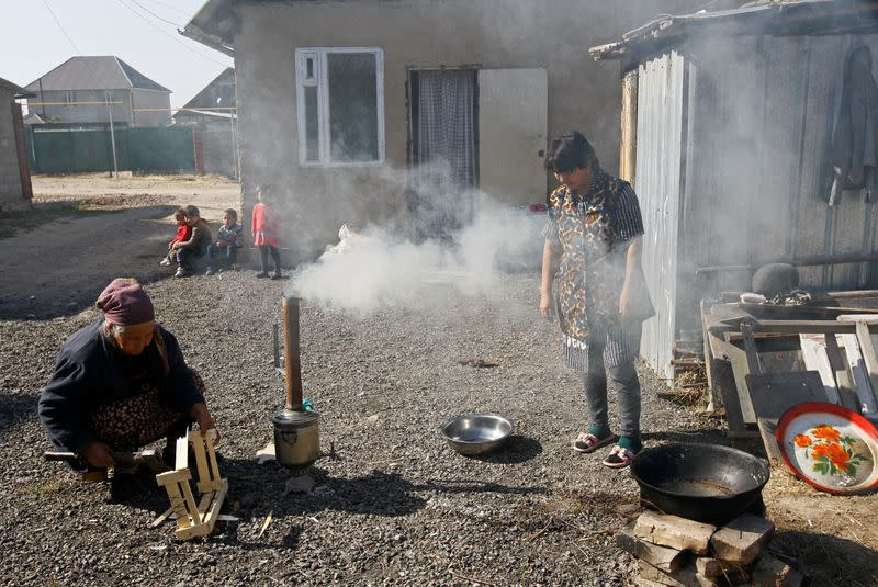 Pensioner Rakya Kudaiberdiyeva uses a samovar to boil water outside her family's rented house in Bishkek