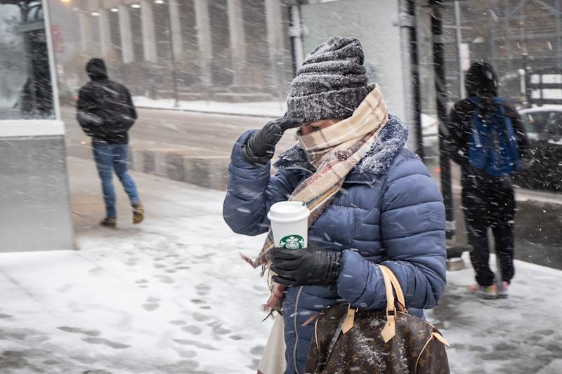 Commuters walk in the snow as a winter weather advisory is issued for the Chicago area on Monday, Nov. 11, 2019, in Chicago