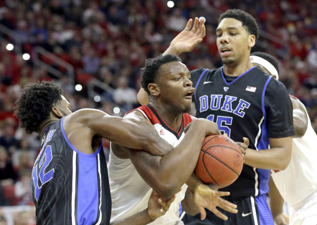 Duke's Justise Winslow, left, and Jahlil Okafor (15) guard North Carolina State's Beejay Anya during the first half of an NCAA college basketball game in Raleigh, N.C., Sunday, Jan. 11, 2015. (AP Photo/Gerry Broome)