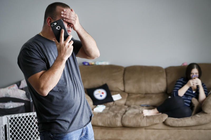 FILE - In this Nov. 28, 2018, file photo Tom Wolikow, a General Motors employee who is currently laid-off, left, takes a phone call at home alongside his fiance Rochelle Carlisle in Warren, Ohio. An economic renaissance in the industrial Midwest promised by President Donald Trump has suffered in recent weeks in ways that could be problematic for Trump's 2020 re-election. (AP Photo/John Minchillo, File)