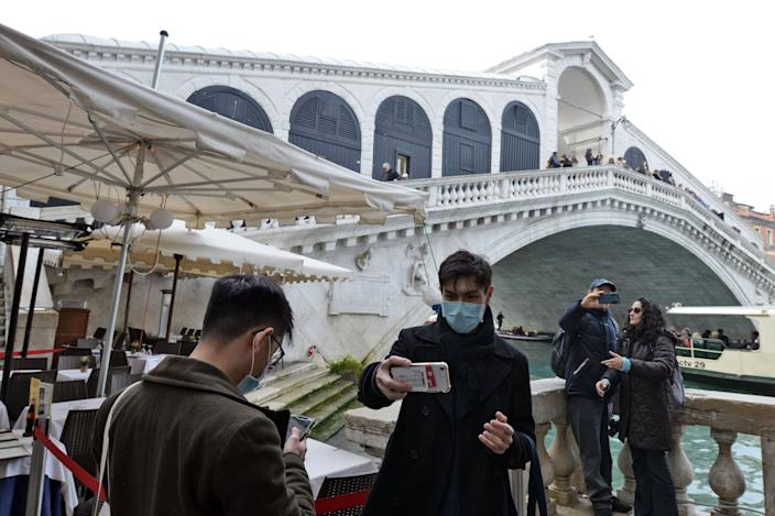 Tourists pose for selfies in front of the Rialto bridge in Venice after the carnival was canceled due to a coronavirus outbreak in Italy, on February 24, 2020.