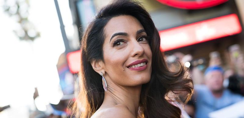 Amal Clooney looks over her shoulder and smiles at the red carpet.