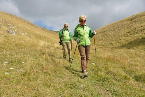 """<span class=""""caption"""">Eccentric exercises (such as walking downhill) cause our muscles to lengthen under the load in order to slow the body down.</span> <span class=""""attribution""""><a class=""""link rapid-noclick-resp"""" href=""""https://www.shutterstock.com/image-photo/senior-tourist-couple-hiking-beautiful-mountains-770946652"""" rel=""""nofollow noopener"""" target=""""_blank"""" data-ylk=""""slk:FS Stock/Shutterstock"""">FS Stock/Shutterstock</a></span>"""