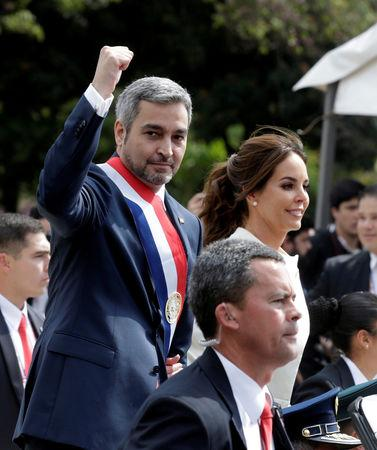FILE PHOTO: Paraguay's new President Mario Abdo Benitez gestures to the public as he rides in an open car alongside Paraguay's first lady Silvana Lopez Moreira after his inauguration ceremony in Asuncion, Paraguay August 15, 2018. REUTERS/Jorge Adorno