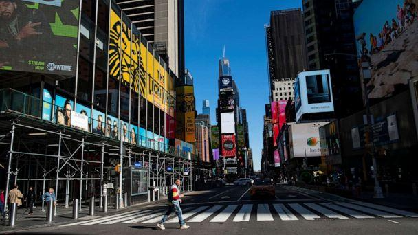 PHOTO: A man crosses a 7 Avenue in a nearly empty Times Square in New York City, March 14, 2020. (Eduardo Munoz/Reuters)