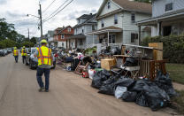 Utility workers walk along a street piled with debris from flood damage caused by the remnants of Hurricane Ida in Manville, N.J., Sunday, Sept. 5, 2021. Flood-stricken families and business owners across the Northeast are hauling waterlogged belongings to the curb and scraping away noxious mud as cleanup from Ida moves into high gear. (AP Photo/Craig Ruttle)