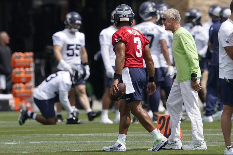 Seattle Seahawks head coach Pete Carroll, right, walks with quarterback Russell Wilson (3) during NFL football practice Wednesday, July 28, 2021, in Renton, Wash. (AP Photo/Ted S. Warren)