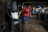 A woman walks into her house, flooded during the passage of Hurricane Iota in Siuna, Nicaragua, Tuesday, Nov. 17, 2020. Hurricane Iota tore across Nicaragua on Tuesday, hours after roaring ashore as a Category 4 storm along almost exactly the same stretch of the Caribbean coast that was recently devastated by an equally powerful hurricane. (AP Photo/Carlos Herrera)