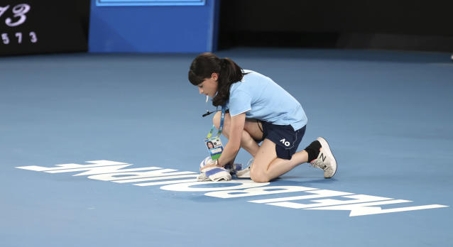 Court staff wipes water from Rod Laver Arena that was dripping from the roof during first round singles matches at the Australian Open tennis championship in Melbourne, Australia, Monday, Jan. 20, 2020. (AP Photo/Lee Jin-man)