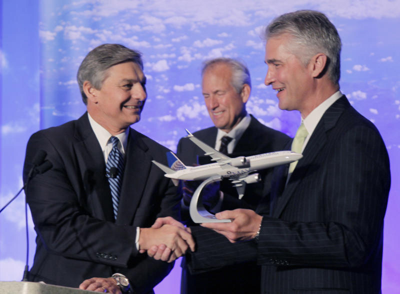 Boeing Commercial Airplanes CEO Ray Conner, left, presents a model of Boeing's new 737 Max 9 to United Airlines CEO Jeff Smisek during a news conference as Boeing CEO Jim McNerney looks on, Thursday, July 12, 2012, in Chicago. United Airlines and Boeing announce that United is buying 150 Boeing 737s, and is planning to use them to replace older planes that are not as fuel efficient. (AP Photo/M. Spencer Green)