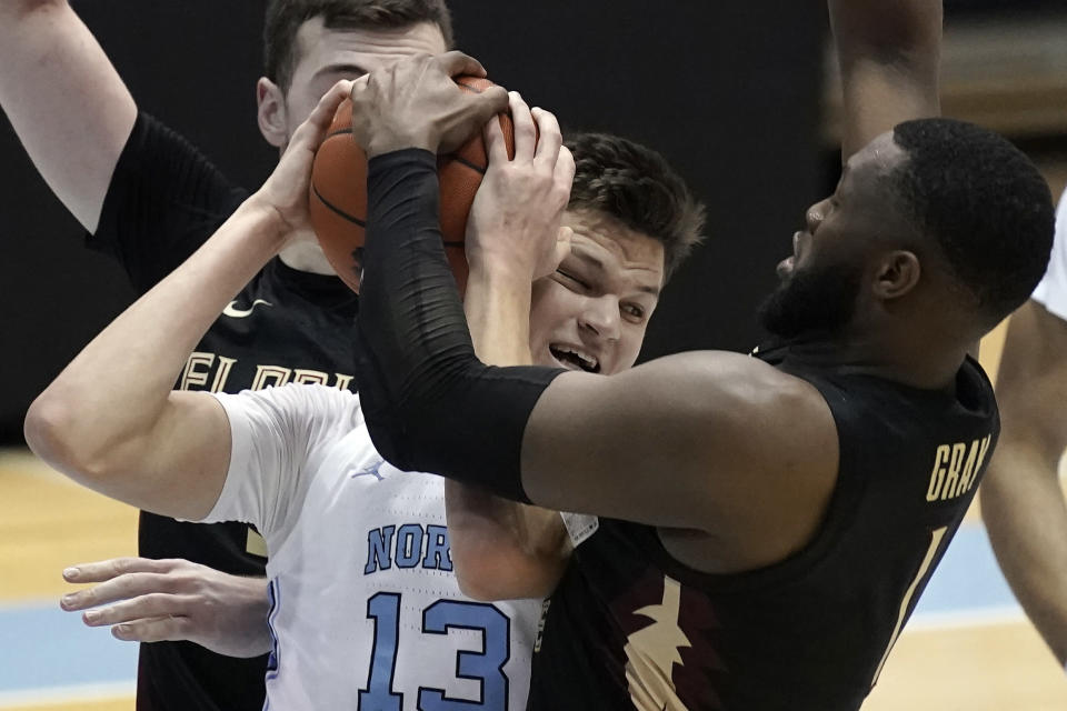 Florida State forward RaiQuan Gray (1) and North Carolina forward Walker Kessler (13) struggle for the ball during the first half of an NCAA college basketball game in Chapel Hill, N.C., Saturday, Feb. 27, 2021. (AP Photo/Gerry Broome)