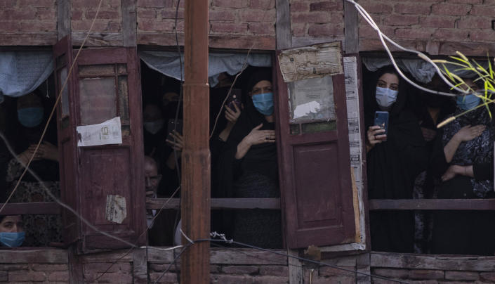 Kashmiri Shiite Muslims wearing face masks watch a Muharram procession from a residential house in Srinagar, Indian controlled Kashmir, Saturday, Aug. 29, 2020. Muharram is a month of mourning in remembrance of the martyrdom of Imam Hussein, the grandson of Prophet Mohammed. Authorities had imposed restrictions in parts of Srinagar, the region's main city, to prevent gatherings marking Muharram from developing into anti-India protests. (AP Photo/Mukhtar Khan)