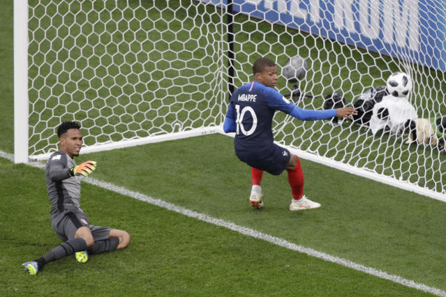 France's Kylian Mbappe, right, scores the opening goal past Peru goalkeeper Pedro Gallese during the group C match between France and Peru at the 2018 soccer World Cup in the Yekaterinburg Arena in Yekaterinburg, Russia, Thursday, June 21, 2018. (AP Photo/Mark Baker)