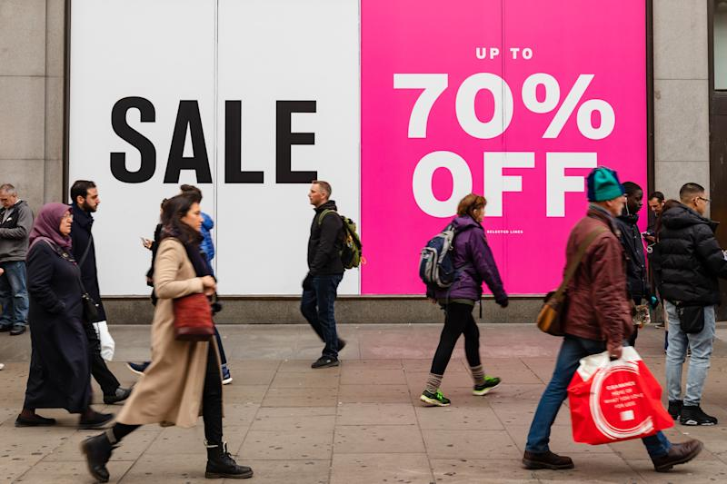 People walk past clothes shop displaying a 70% off sale sign in Oxford Street, London, UK on January 03, 2019 (photo by Vickie Flores/In Pictures via Getty Images)