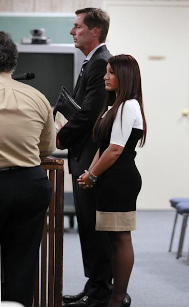 """Jersey Shore"" cast member Deena Cortese, right, stands with her attprney Michael Pappa, center back, during a hearing Tuesday, July, 3, 2012, in Seaside Heights, N.J. Police arrested Cortese on June 10, saying she was dancing in a roadway and interfering with the flow of traffic. But municipal prosecutor Kim Pascarella said the prosecution did not have enough evidence to prove that charge, agreeing instead to allow her to plead guilty to the lesser offense of not using a sidewalk when one was provided. She pleaded guilty to failing to use the sidewalk and paid a $106 fine. (AP Photo/Mel Evans)"